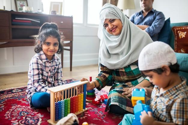Familia musulmana relajante y jugando en casa