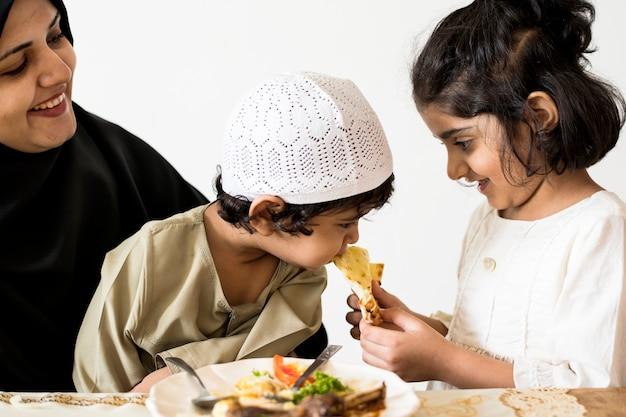Familia musulmana teniendo una comida