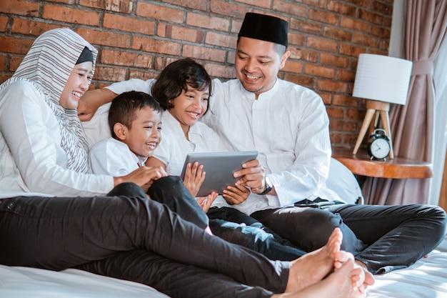 Familia musulmana usando tableta juntos