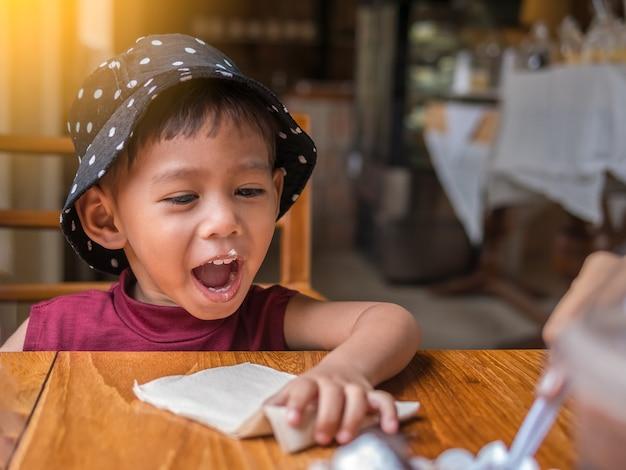 Familia muy divertida del bebé de panadería de alimentación de la madre asiática a su hija linda en el café.
