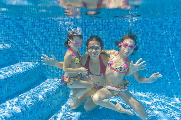 Familia nadar en la piscina bajo el agua