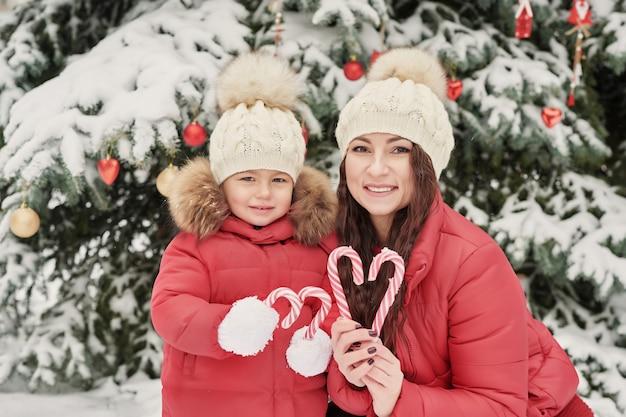 Familia de navidad en el parque de invierno. la familia feliz y la hija del niño que se divierten, jugando en invierno caminan al aire libre diversión familiar al aire libre en vacaciones de navidad. ropa de invierno para bebés y niños pequeños.