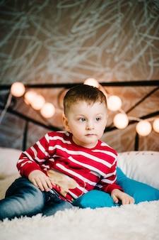 Familia navideña! hijo feliz en suéteres de santa claus, juega con almohadas.