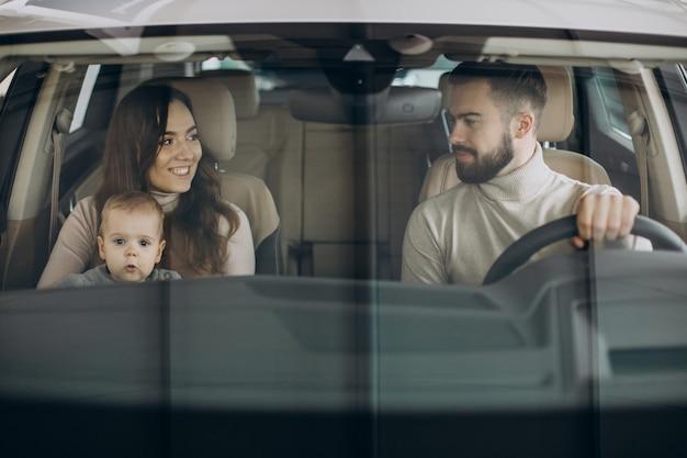 Familia con niña bbay eligiendo un coche en una berlina.