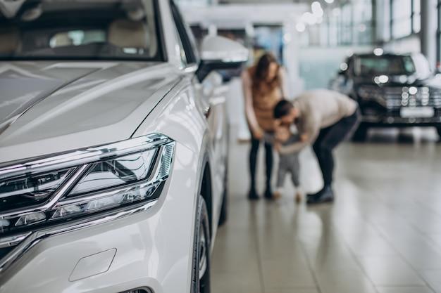 Familia con niña eligiendo un coche en un salón de autos