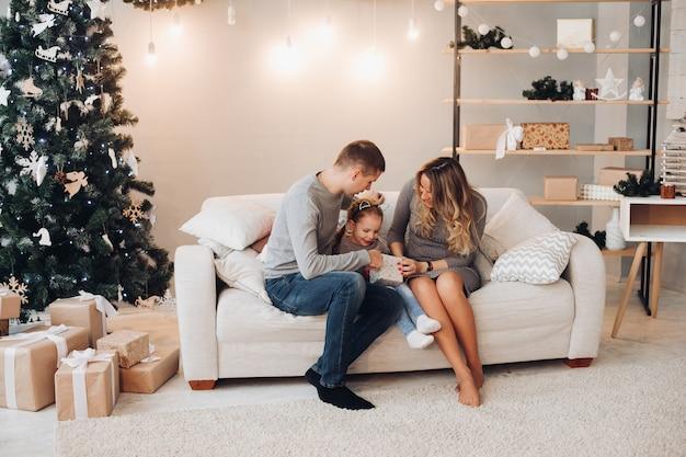 Familia con niño abriendo regalo de navidad. árbol de navidad.