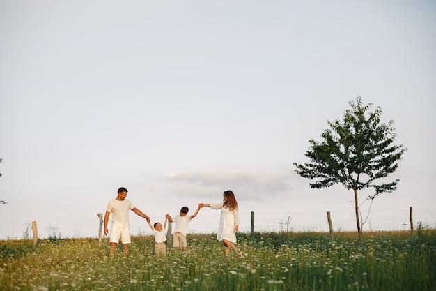 Familia con niño lindo. padre con camiseta blanca. fondo del atardecer.