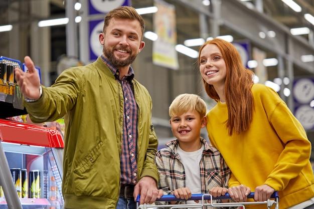 Familia con niño en la tienda de comestibles, familia en la tienda. padres e hijos en un centro comercial eligiendo comida. comida sana.