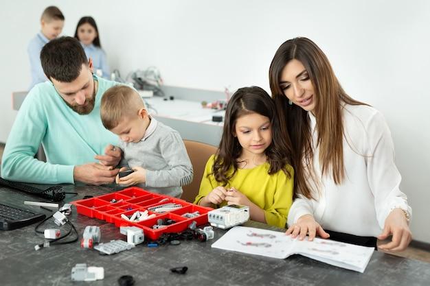 Una familia con niños en un club de robótica fabrica un robot controlado por un constructor.