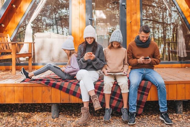 Familia con niños en el día de otoño, cada uno con su propio dispositivo al aire libre