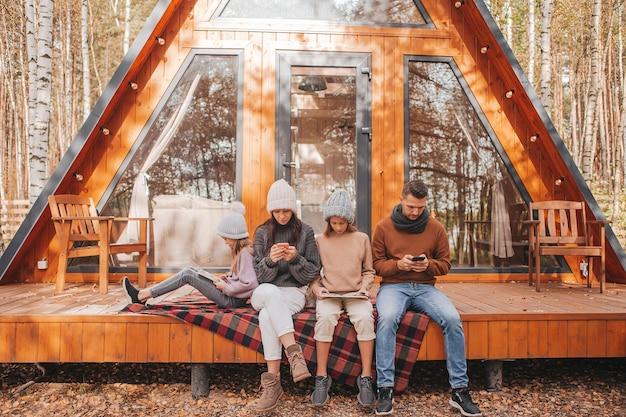 Familia con niños en la terraza de su casa en un día de otoño, cada uno con su propio gadget