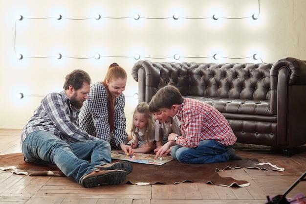Familia numerosa feliz jugando juego de mesa.