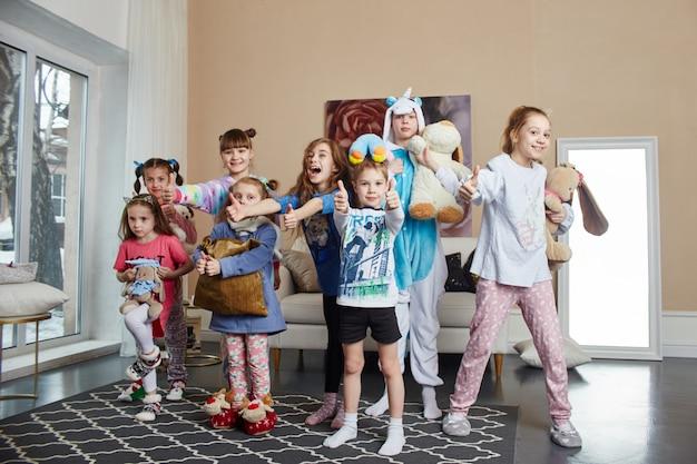 Familia numerosa, los niños se divierten y juegan en la mañana en casa. chicos y chicas en pijama nocturno
