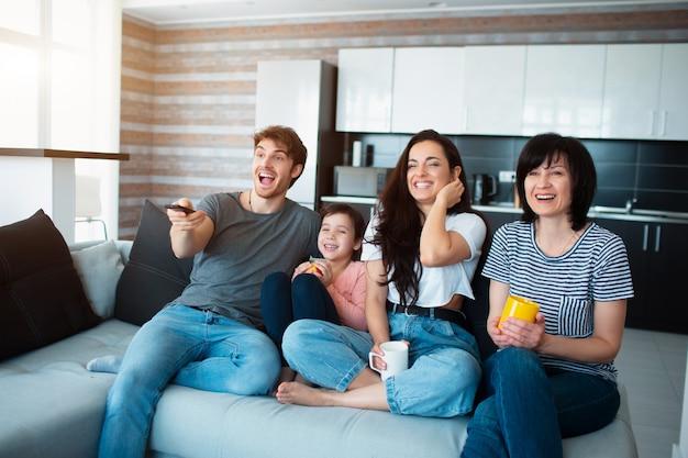 Una familia numerosa está viendo la televisión. hermanos, hermanas, madre, abuela y nieta bebé.