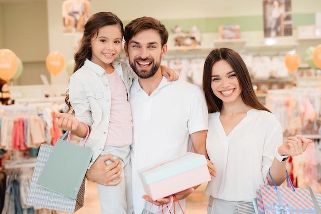 Familia, padre, madre e hija con bolsas de la compra.