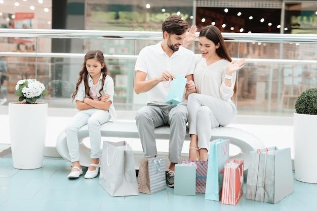 Familia, padre, madre e hija están sentados en un banco.