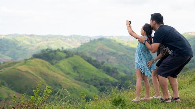 Familia de padre, madre e hija tomando selfie en la cima de la montaña