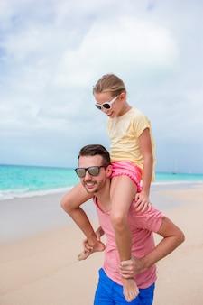 Familia de padre y niña deportiva divirtiéndose en la playa