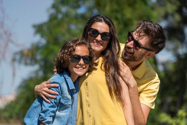 Familia con padres e hijo posando juntos en el parque