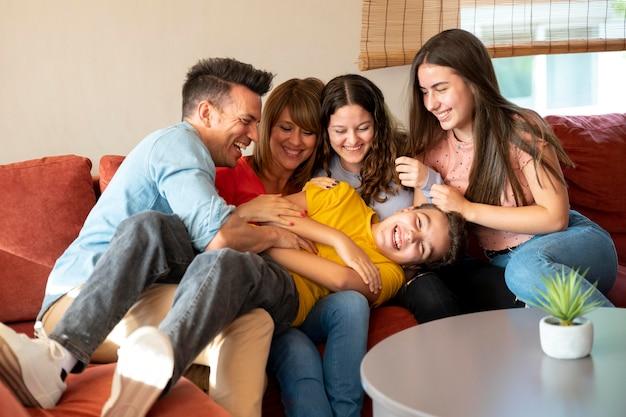 Familia con padres e hijos divirtiéndose juntos en el sofá