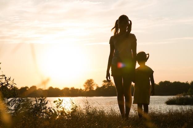 Familia de padres e hijos siluetas al atardecer al aire libre