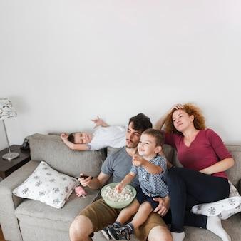 Familia con palomitas viendo televisión en casa.