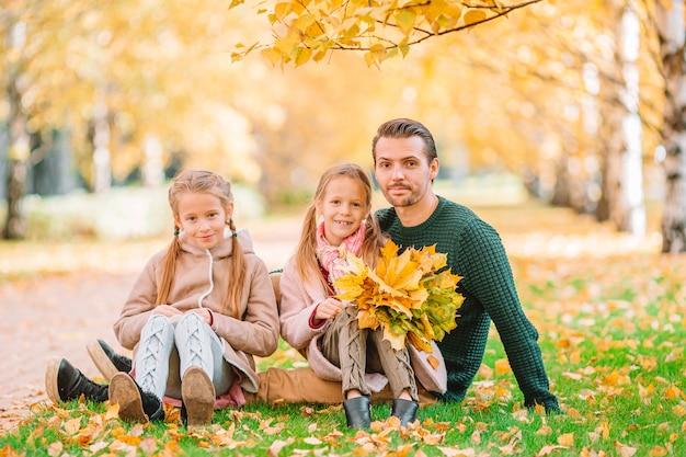 Familia de papá e hijos en un hermoso día de otoño en el parque