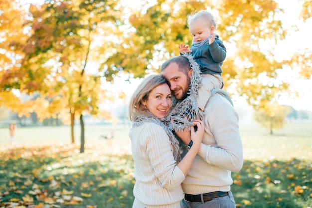 Familia pareja abrazándose en el parque al aire libre con su bebé sentado sobre los hombros de los padres
