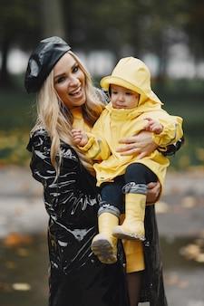 Familia en un parque lluvioso. niño con impermeables amarillos y mujer con abrigo negro.