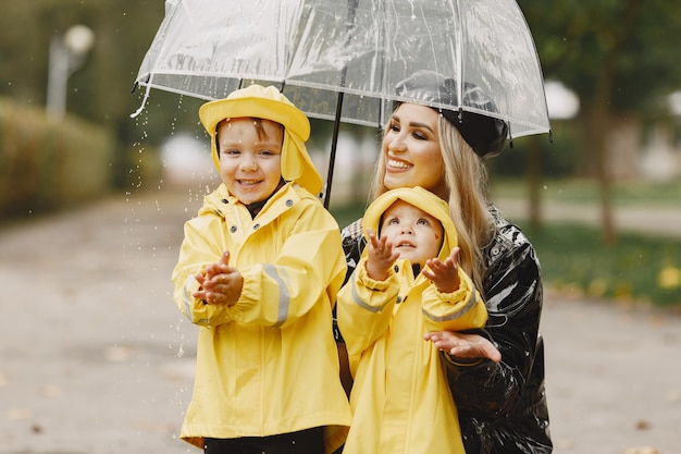 Familia en un parque lluvioso. niños con impermeables amarillos y mujer con abrigo negro.