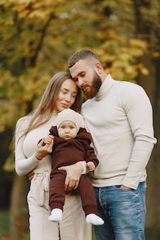 Familia en un parque de otoño. hombre con un suéter marrón. niña linda con sus padres.
