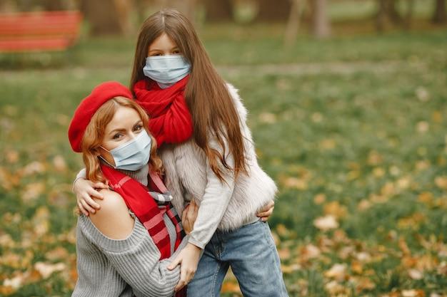 Familia en un parque de otoño. tema de coronavirus. madre con hija.