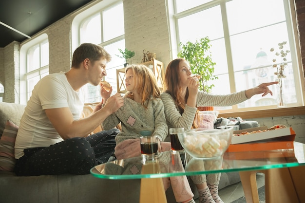 La familia pasa un buen rato juntos en casa, se ve feliz y emocionada, comiendo pizza, viendo partidos deportivos