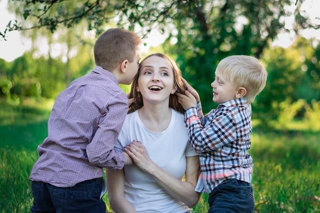 Familia pasando un buen rato en el parque. los hijos juegan con mamá. concepto de infancia y paternidad feliz