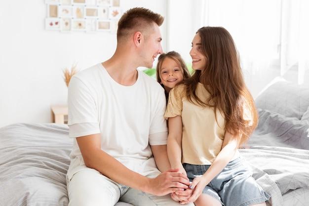 Familia pasando tiempo juntos en el dormitorio.