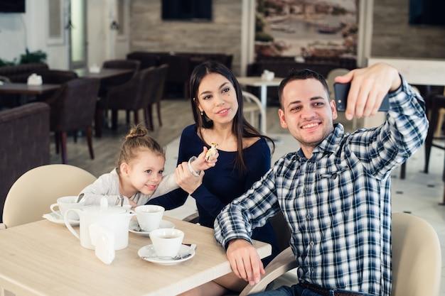 Familia, paternidad, concepto de personas de tecnología: madre feliz, padre y niña cenando tomando selfie por teléfono en el restaurante