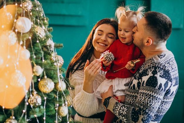 Familia con pequeña hija colgando juguetes en el árbol de navidad