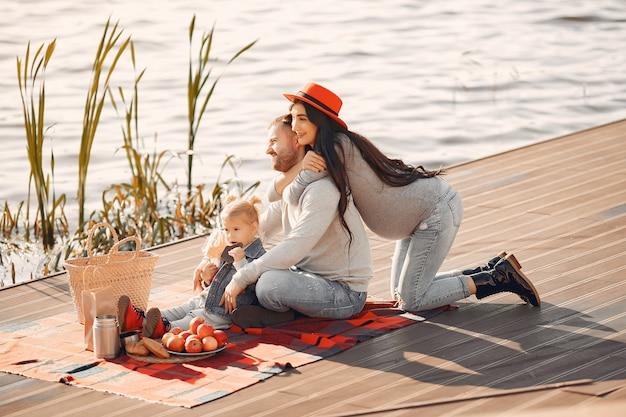 Familia con pequeña hija sentada cerca del agua en un parque de otoño