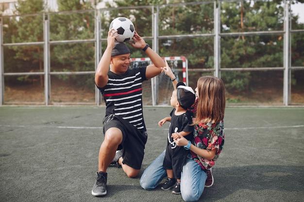 Familia con pequeño hijo jugando al fútbol