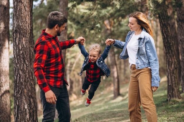 Familia con pequeño hijo juntos en el bosque