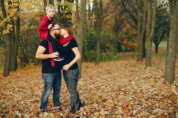 Familia con pequeño hijo en un parque de otoño