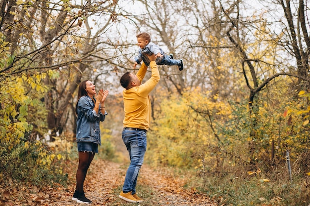 Familia con un pequeño hijo en el parque otoño
