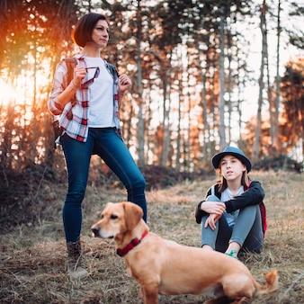 Familia con perro descansando en el bosque durante el atardecer