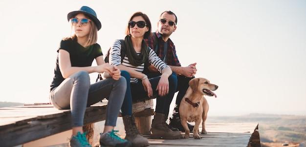 Familia con perro descansando sobre una terraza de madera después de caminar