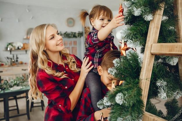 Familia de pie en casa cerca del árbol de navidad