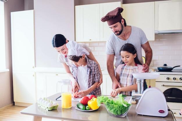 La familia está de pie en la cocina y cocinando. guy ayuda a la niña a cortar el pepino.