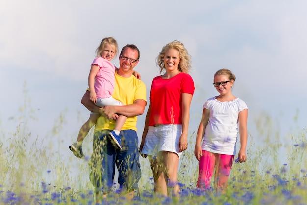 Familia de pie en la pradera en verano con flores, el padre lleva a su hija