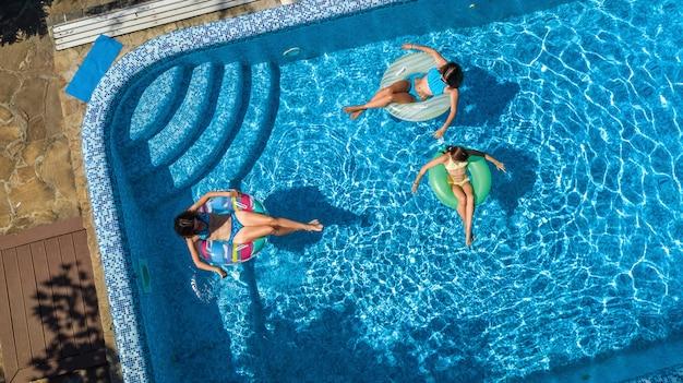 Familia en la piscina vista aérea de aviones no tripulados desde arriba, feliz madre e hijos nadan en anillos inflables y se divierten en el agua en vacaciones familiares, vacaciones tropicales en el resort