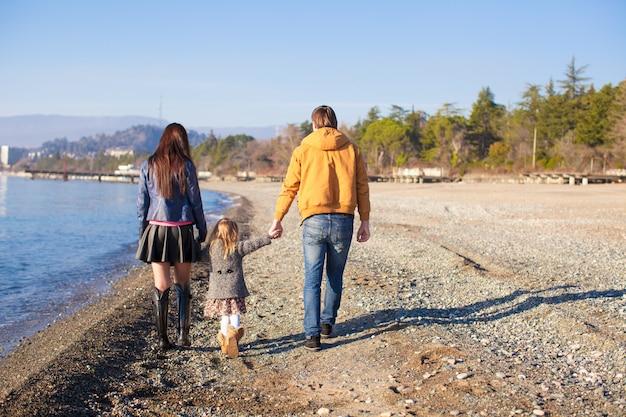Familia en la playa salvaje durante el cálido invierno