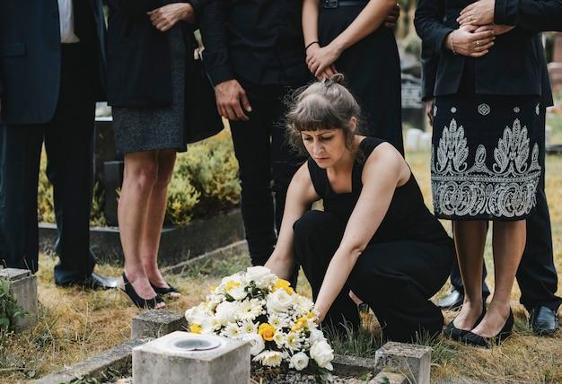 Familia poniendo flores en la tumba